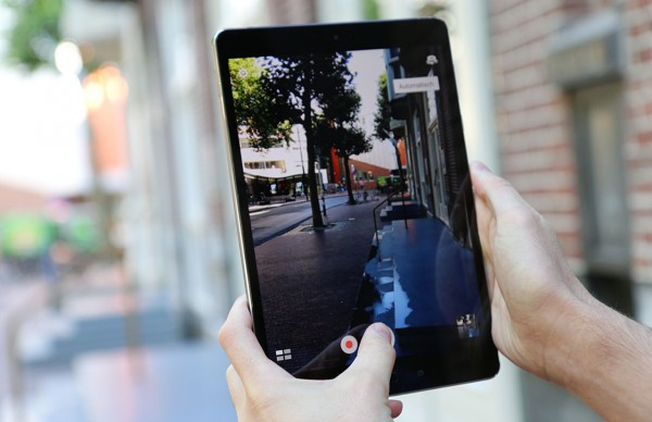asus zenpad 3s 10 (z500m) in twee handen foto makend van een winkelstraat met bomen