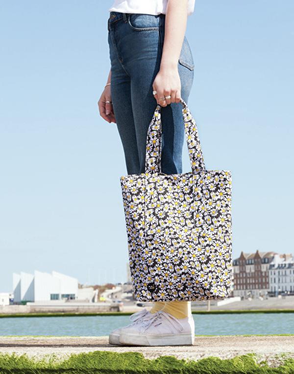 vrouw aan de rand van een rivier met bloemige tote bag in haar hand