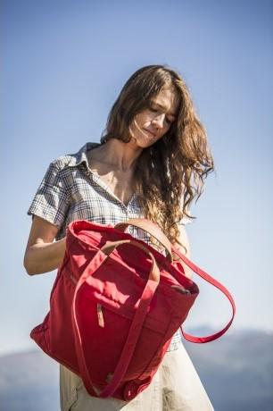 vrouw met rode tote bag in haar hand