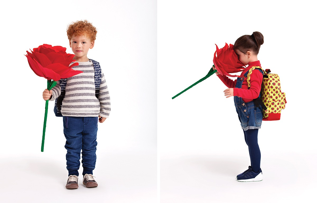 jongetje met roos in de hand en kinderrugzak op zijn rug, meisje ruikt aan de roos en heeft een gele kinderrugzak op haar rug