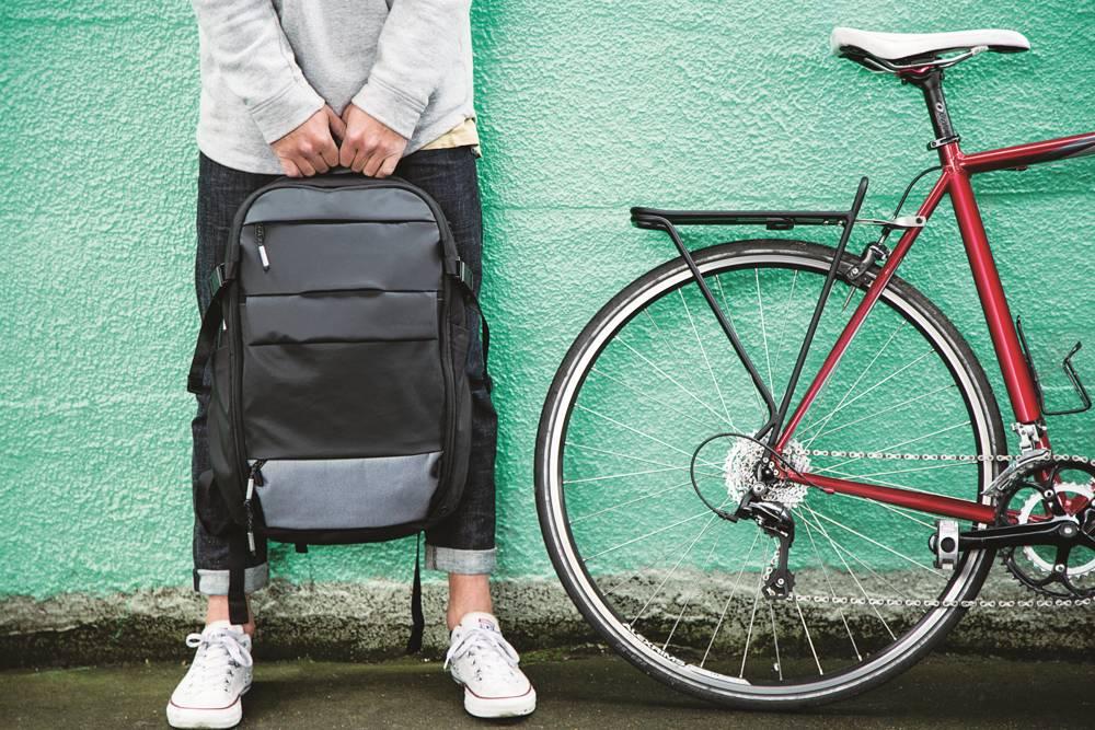 persoon met laptoprugzak in de hang met een fiets ernaast voor een groene muur