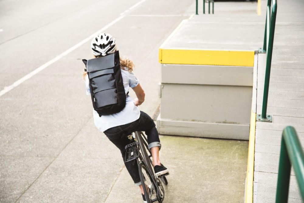 vrouw op de fiets met een laptoprugzak op haar rug