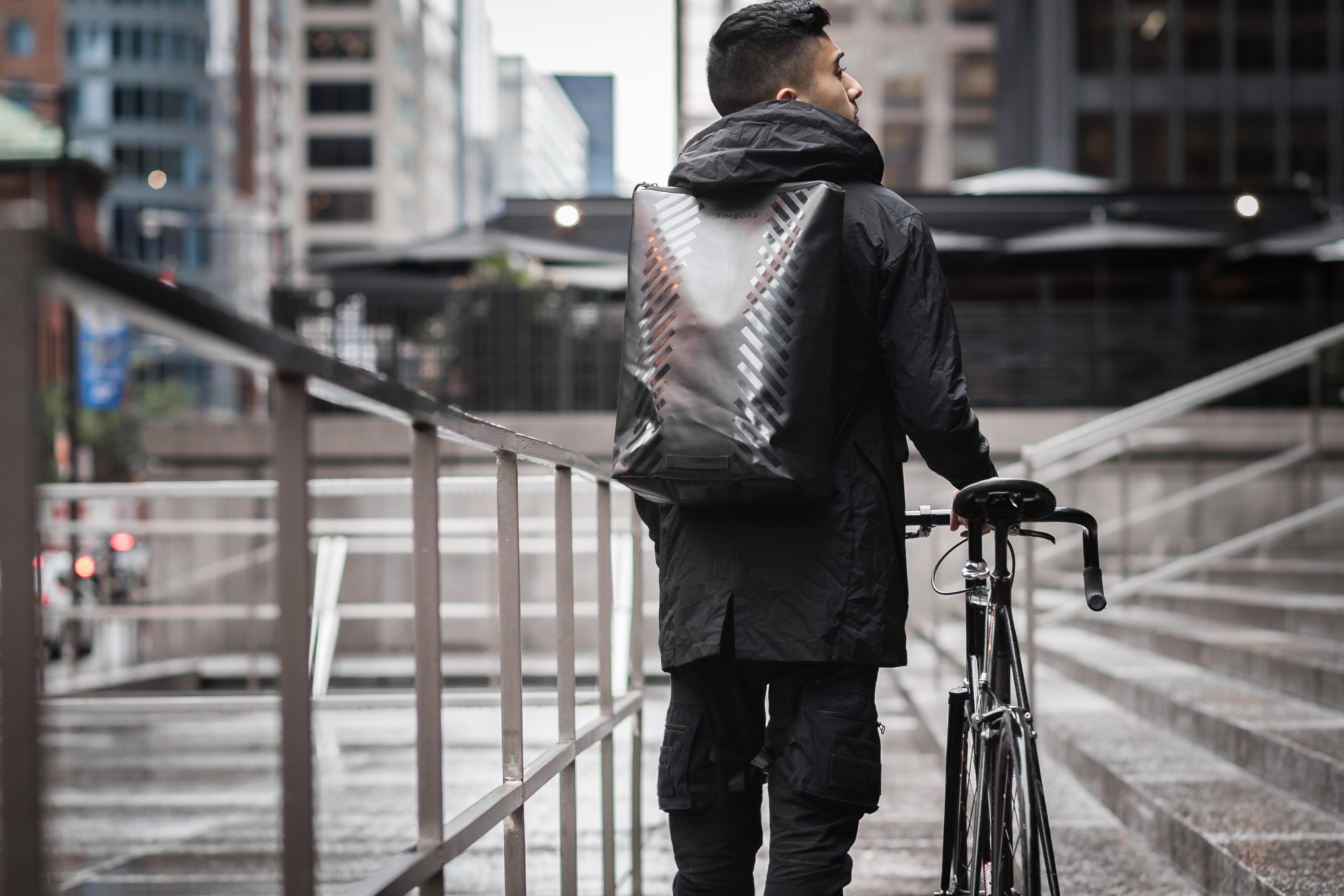 jongen met rugzak op de rug en fiets in de hand loopt langs gebouw