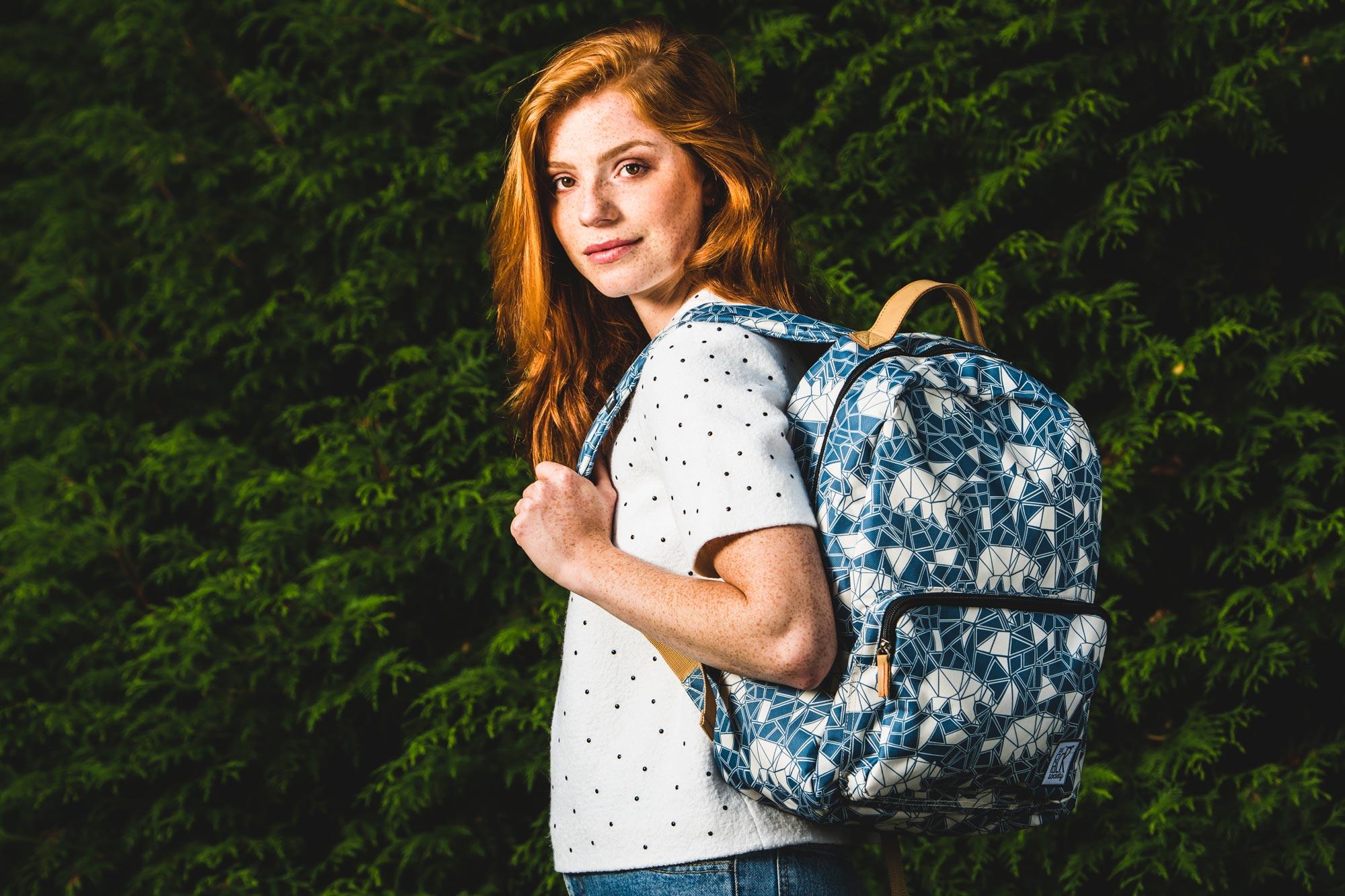 een meisje met een schoolrugzak voor een heg