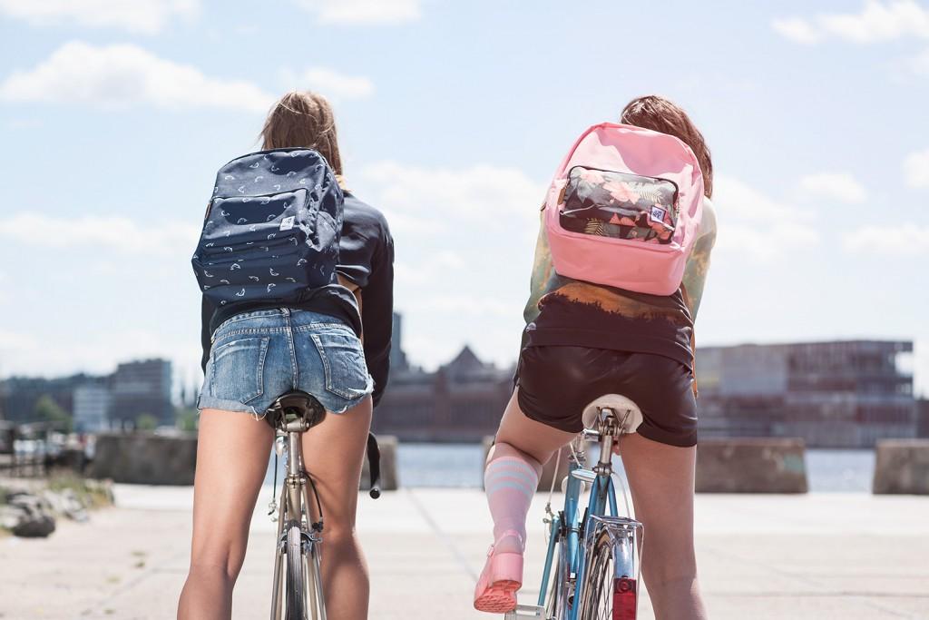twee meisjes op de fiets met allebei een schoolrugzakken op de rug