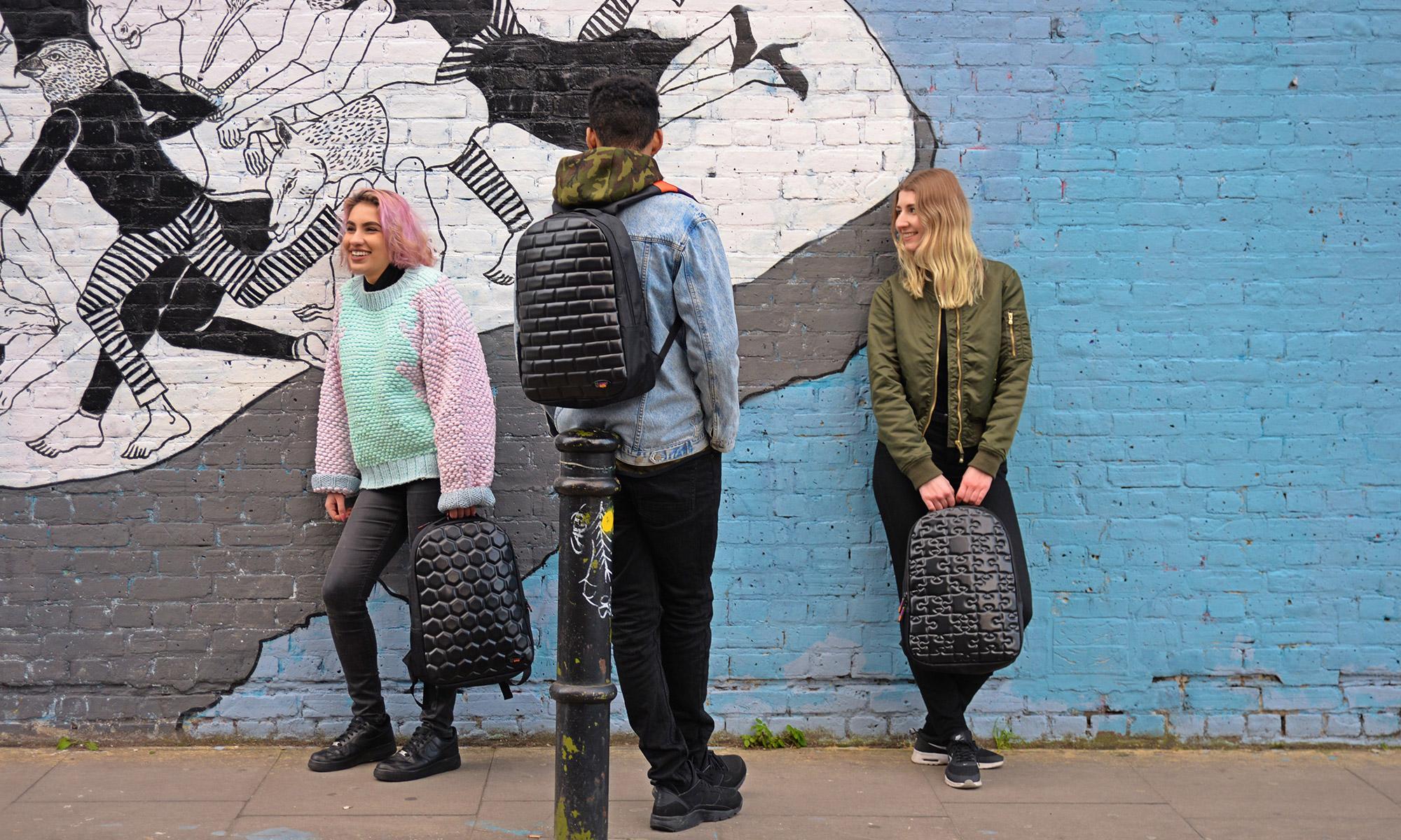 twee meisjes en een jongen met zwarte schoolrugzakken bij een graffiti muur
