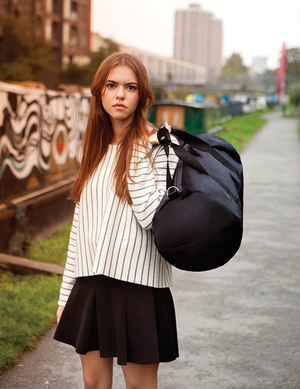 meisje in een park met zwarte duffel weekendtas in de hand