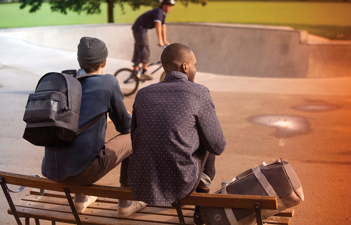 twee jongens op een bankje bij een skatepark met een duffel weekendtas en rugzak