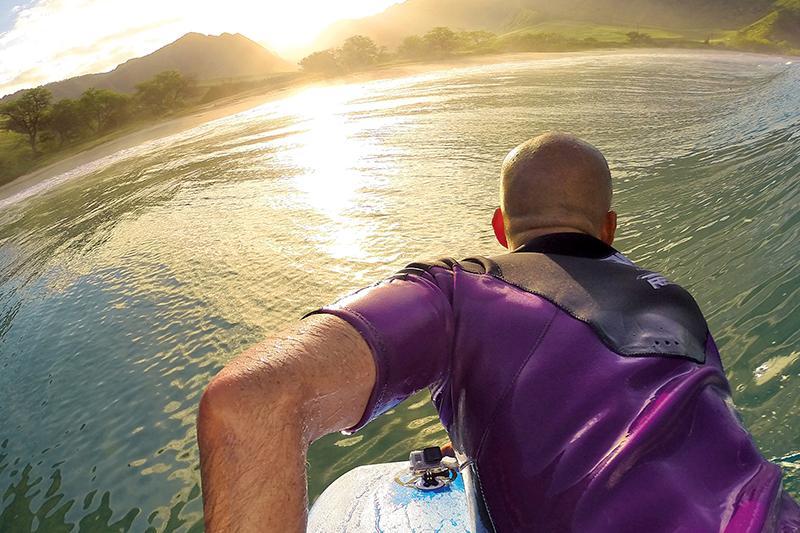 Surfer met een GoPro hero6 action cam gemonteerd op zijn surfboard