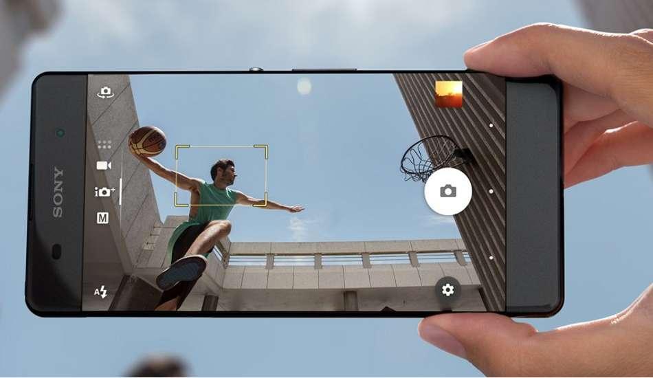 zwarte sony xperia xz in de hand foto makend van basketballer tussen gebouwendie een doelpoging doet